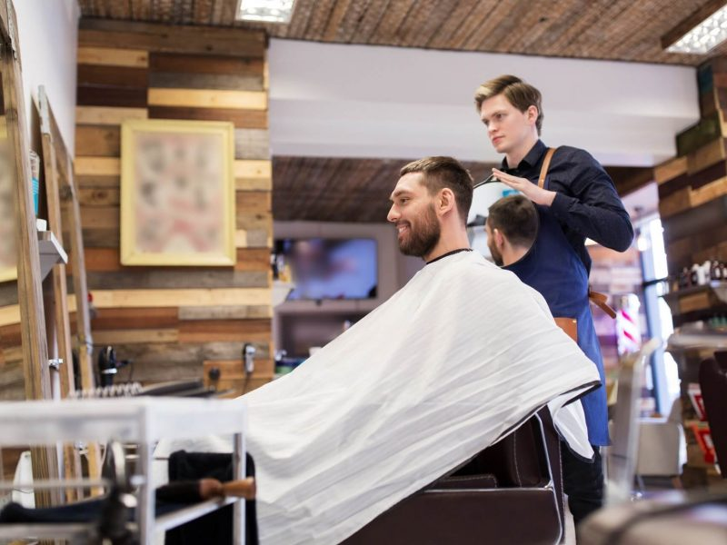 man-and-hairdresser-with-mirror-at-barbershop.jpg